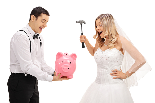 bride and groom about to break a piggy bank to pay for their wedding